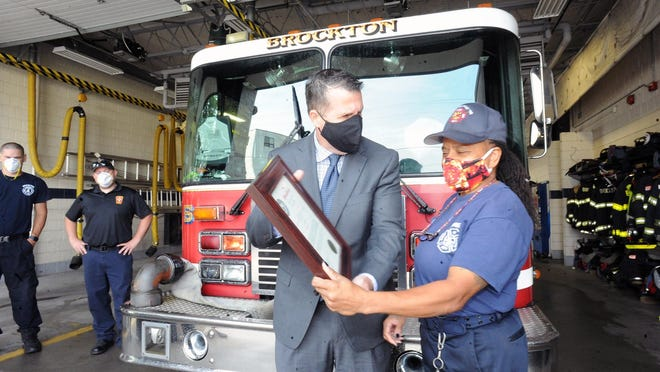 Brockton mayor Robert Sullivan, presents Brockton firefighter Carol E. Dawkins with a citation for her twenty one years of service to her community at Station 6, on Tuesday, Aug. 25, 2020.  Carol was Brockton's first female firefighter and that was her last work shift.
