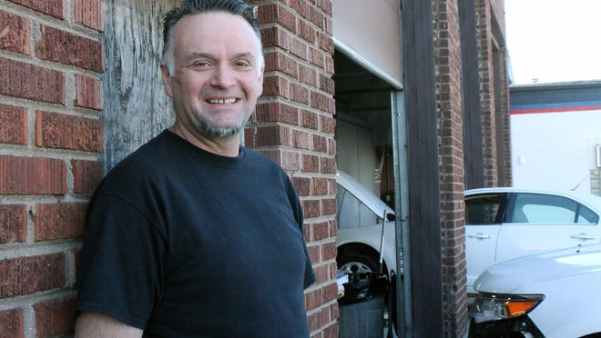 Kewanee High School basketball coach Shaune Lewis stands outside his auto body business. With high school sports on the shelf because of the novel coronavirus, Lewis threw himself back into a longstanding passion: auto racing.