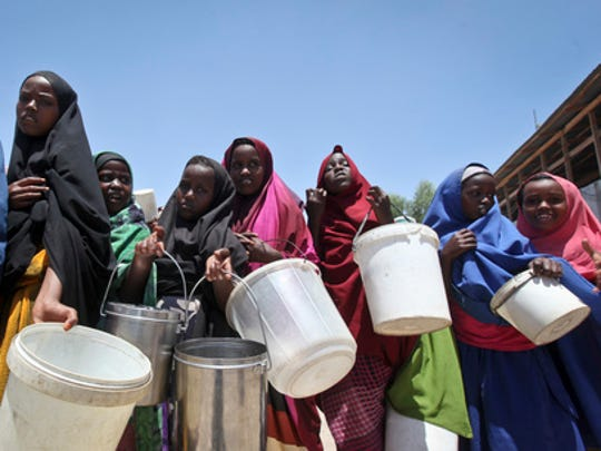 FILE - In this Saturday, Feb. 25, 2017 file photo, displaced Somali girls who fled the drought in southern Somalia stand in a queue to receive food handouts at a feeding center in a camp in Mogadishu, Somalia. Somalia's prime minister said Saturday, March 4, 2017 that 110 people have died from hunger in the past 48 hours in a single region as a severe drought threatens millions of people.