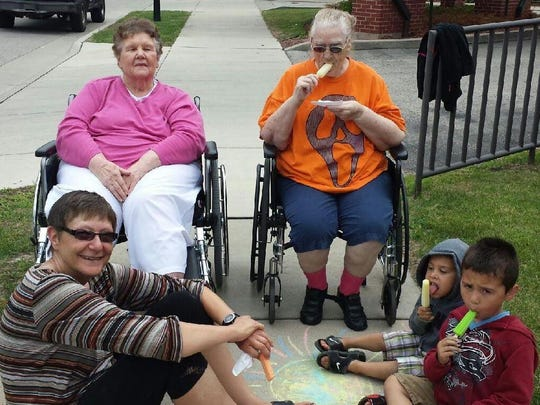 Residents from Lutheran Home & Health Services enjoyed watchng as budding artists decorated the sidewalk in front of the home with colorful rainbows, flowers and suns. From left: Jill Stiemsma, Mary Schmidt, Stella Burns, Miguel Luna, 4, and Mason Luna, 5.