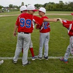 Hunter Richardson and Braylon Essian fist bump during a 10-and-under baseball game victory Saturday in St. Clair.