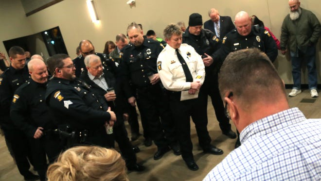 Community members gather around local law enforcement in prayer during a vigil for the two police officers who were killed in Westerville last week. The vigil took place at Crossroads Church's City Center.