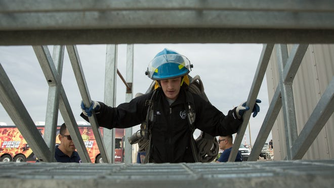 Wearing fire fighting equipment, Zach Huggins, a defensemen with the El Paso Rhinos Hockey team, takes to the stairs for the stair climb test, the final drill in the timed course, Saturday, February 18, 2017.