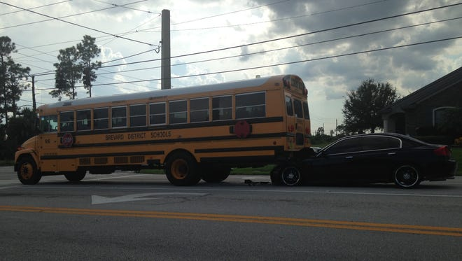 A car is lodged under a school bus after a crash in Palm Bay.