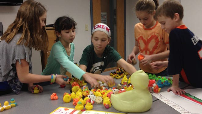 Holt Public Schools students, from left, Cortney Morgan, Julia Toomey, Nadia Weise, Paige Lemmon and Sawyer Hosford sort rubber ducks last week at Washington Woods Middle School. The ducks will be sold to fund a truck full of bottled water for Flint residents. Also part of the effort are  Rodney Stewart and Lily Stroud.