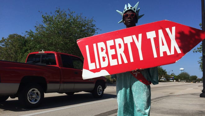 Michael Moss holds a sign Monday promoting the Liberty Tax Service location on Dr. Martin Luther King Jr. Boulevard, near downtown Fort Myers.