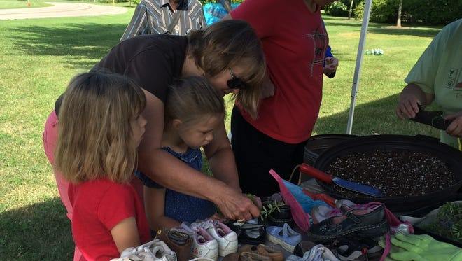 Rita Kranig  helps her granddaughters Nikki, left, and Tasha Ludwig place plants in old children's shoes at Prairie Fest Saturday morning.