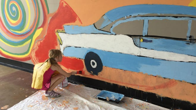 """""""Childtime summer camper Sarah Sawicki 8 years old, helps paint the background of a large mural on the wall of a vacant building that will be used during Beaumont's Cruise & View Fundraising event for Children's Miracle Network on Saturday, August 20."""