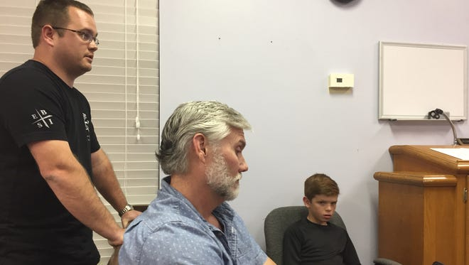 Sterlington police officer Melvin Cooper Jr. (standing) on Tuesday told the Board of Alderman that his doctor said he could return to work months ago. Cooper said he was injured in the same wreck that killed Sgt. David Elahi but has not been allowed to return to work and Chief Barry Bonner (seated) has not answered his requests for information.