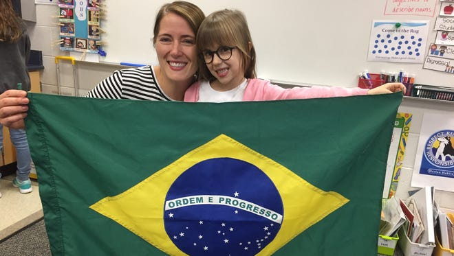 Diane Oliveira and her daughter Stella display the flag of Brazil for Stella's first-grade classmates at Harlan School prior to their move to Brazil.