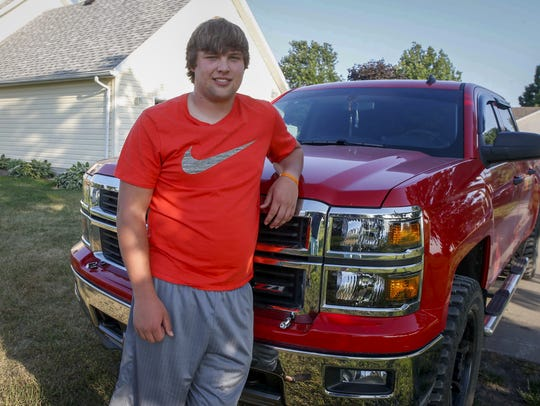 Hunter McWhirter poses for a photo next to his truck