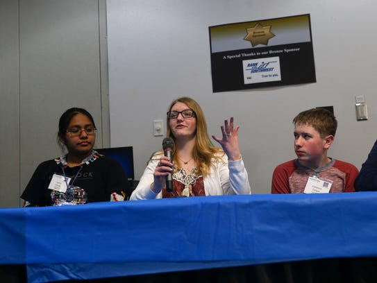 At center Bree Morrow, a 9th grader at San Juan College High School answers a question during a youth panel Feb. 22 during the annual CyberCon at San Juan College in Farmington.