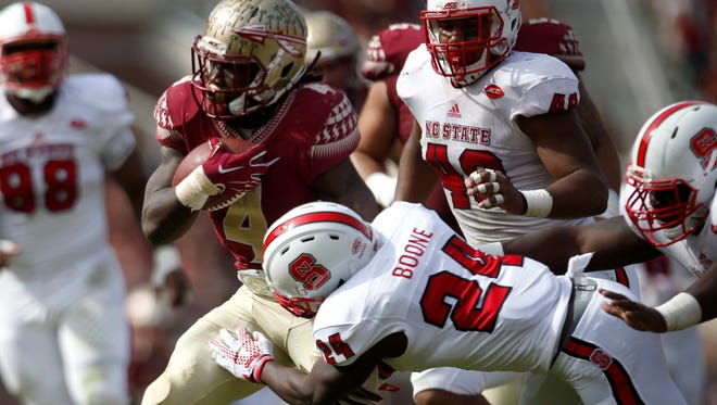 FSU's Dalvin Cook runs past NC State defenders, including Shawn Boone (24) for a touchdown, one of two rushing TD's in the game for Cook who broke Warrick Dunn's single season rushing record during the game at Doak Campbell Stadium on Saturday.