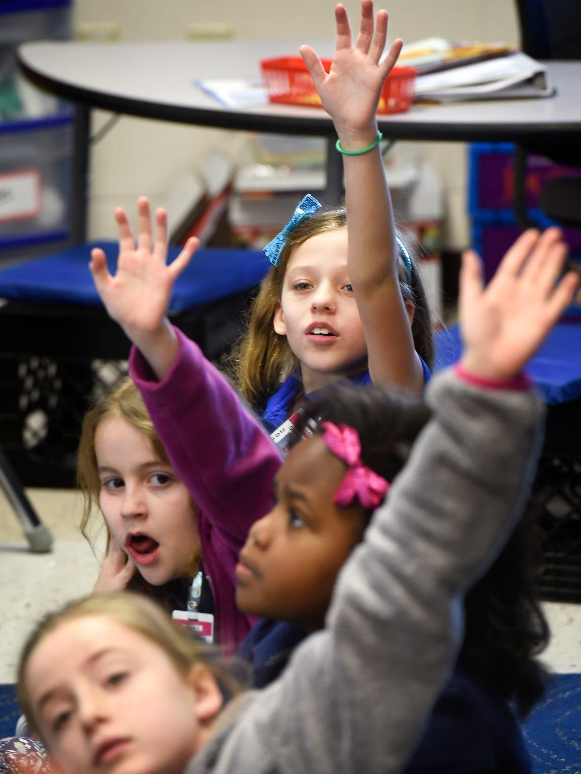 Third-graders in Andrea Davis' class raise their hands