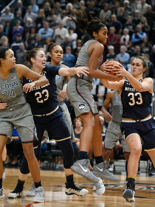Connecticut's Megan Walker, center, pulls down a rebound against Notre Dame's Kathryn Westbeld, right, as Connecticut's Napheesa Collier, left, and Notre Dame's Jessica Shepard, second from left, defend during the second half an NCAA college basketball game, Sunday, Dec. 3, 2017, in Hartford, Conn. (AP Photo/Jessica Hill)