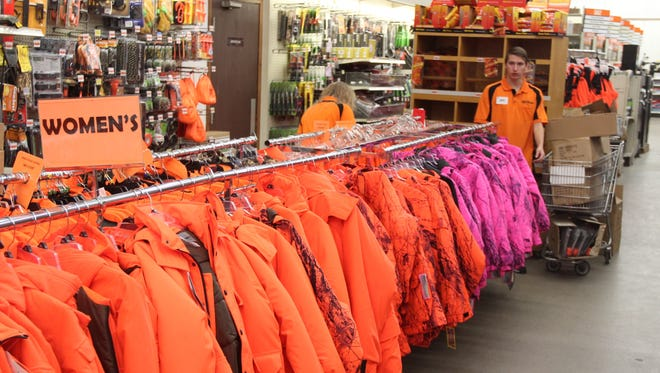 Some blaze pink hunting coats are displayed along with blaze orange clothing at Mills Fleet Farm in Menomonee Falls, Wis.