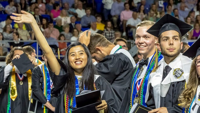 After receiving her diploma and before the graduating seniors march out of Murphy Center, Angelica Bautista of Central Magnet School makes eye contact with members of her family and gives them a wave.
