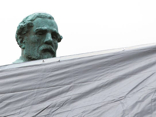 City workers drape a tarp over the statue of Confederate