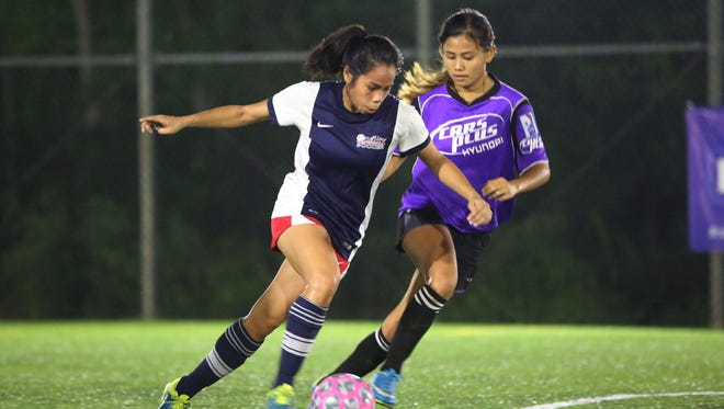 Quality Distributors FC's April Talledo attempts to sprint with the ball past Hyundai's Arisa Recella during a semifinal match of the 2016 Bud Light Women's Futsal League at the Guam Football Association National Training Center futsal courts Sunday. Hyundai advanced to the league's championship match with an 8-6 win after extra time.