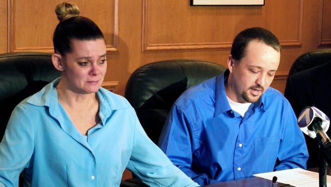 Missie McGuire, left, listens to her husband, Dennis McGuire, at a news conference where they announced their planned lawsuit against the state over the unusually slow execution of his father, also named Dennis McGuire, in Dayton, Ohio.
