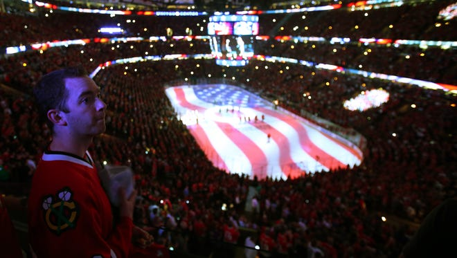 A fan sings the national anthem before game six of the Western Conference Final of the 2015 Stanley Cup Playoffs between the Anaheim Ducks and the Chicago Blackhawks at United Center.