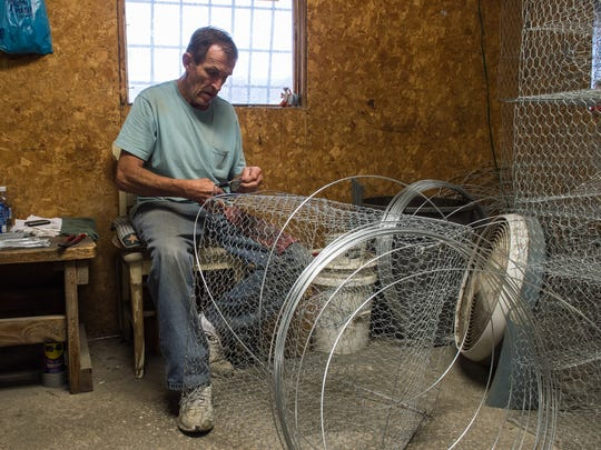 Larry Sterling assembles a crab pot at Heath Crab Pots on West Main Street in Crisfield on Monday, July 17, 2017.