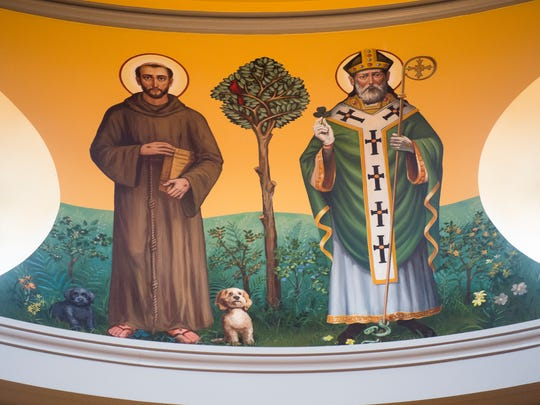 St. Francis of Assisi, left, is painted with Bishop Richard Stika's pet cockapoo dogs, Molly, left, and Rosie, inside the new Cathedral of the Most Sacred Heart of Jesus on Northshore Drive in Knoxville on Thursday, Feb. 15, 2018.