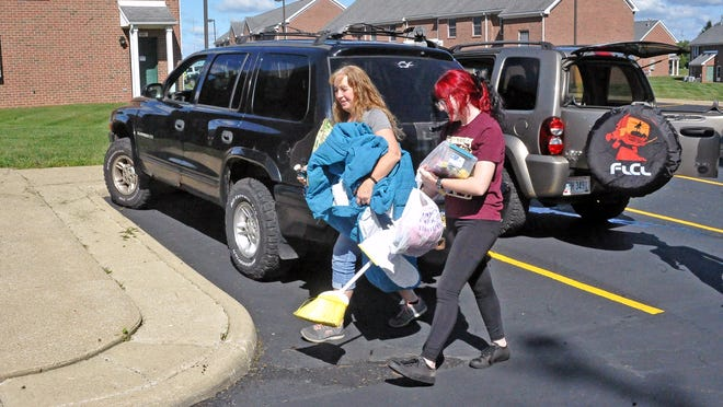 Lynett Caplinger gives her daughter, Maria, a hand moving into the Applewood Village Apartments on Wednesday. Maria, an ATI freshman from New Franklin, will begin classes at the Ohio State University Agricultural Technical Institute on Tuesday.