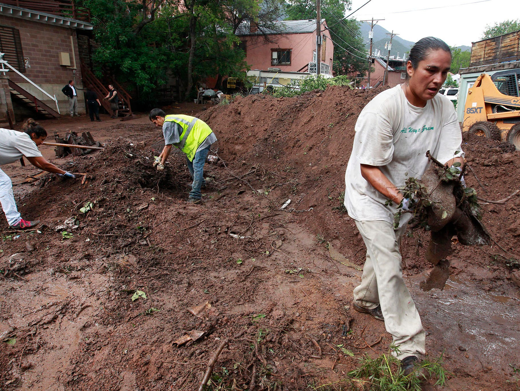 Workers help clear a barrier of mud and debris caused by an Aug. 9 flash flood.
