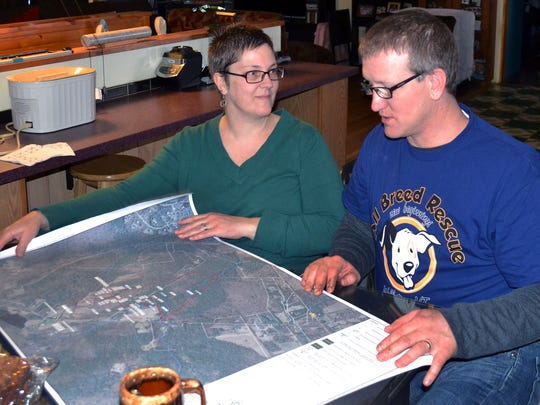 In this Friday, Dec. 16, 2016, photo, Debbie and Richard Higgins, whose well water has been contaminated by a suspected carcinogen from a Dartmouth dump site, look at a map on their kitchen table in Hanover, N.H., which shows where the contamination has spread. Dartmouth College said it has spent  around $8.4 million cleaning up contamination where scientists dumped carcasses of lab animals in the 1960s and 1970s.