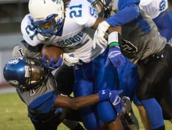 Gary Brightwell carries Howard defenders during St. Georges' 35-14 win over the Wildcats on Sept. 18.