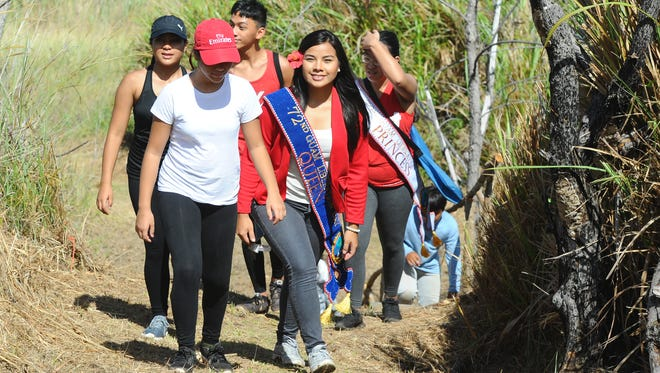 72nd Guam Liberation Queen Alana Chargualaf, front, and members of her royal court, trek up to the Faha Massacre site in Merizo to attend a memorial service on Friday, July 15.