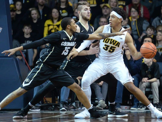 Dec 22, 2017; Sioux Falls, SD, USA; Iowa Hawkeyes forward Cordell Pemsl (35) looks to pass against Colorado Buffaloes guard Dominique Collier (15) and forward Lucas Siewert (23) at Sanford Pentagon. Mandatory Credit: Steven Branscombe-USA TODAY Sports