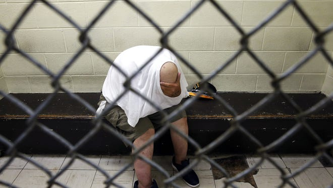 In this June 26, 2014 photo, a U.S. veteran with post-traumatic stress sits in a segregated holding pen at Chicago's Cook County Jail after he was arrested on a narcotics charge.