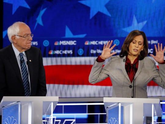 Sen. Kamala Harris, D-Calif., speaks as Sen. Bernie Sanders, I-Vt., listens during the debate Wednesday in Atlanta.