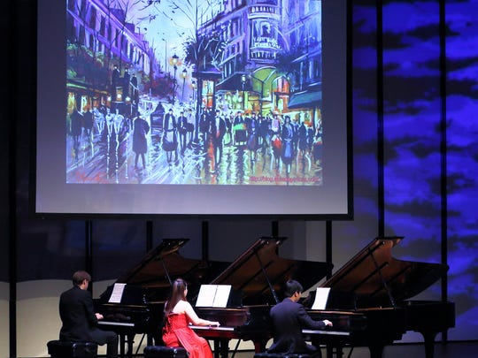 "The giant screen above stage displayed a colorful street scene from ""An American In Paris"" as the three pianists performed a special six-hands arrangement of its music."