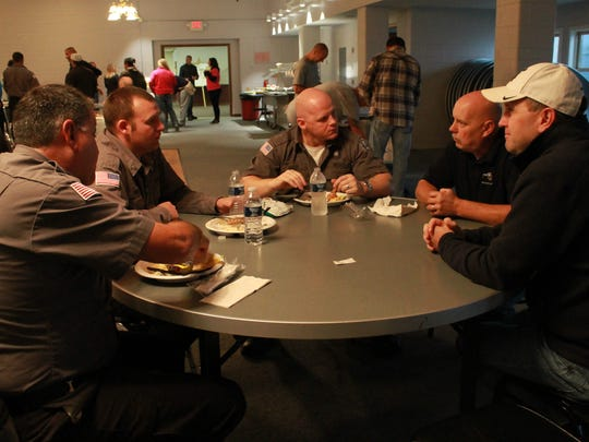 """In this photo provided by the Michigan Corrections Organization, MCO officials speak with corrections officers during an """"appreciation cookout"""" held at Kinross Correctional Facility for prison staff who worked during a September uprising at the prison."""
