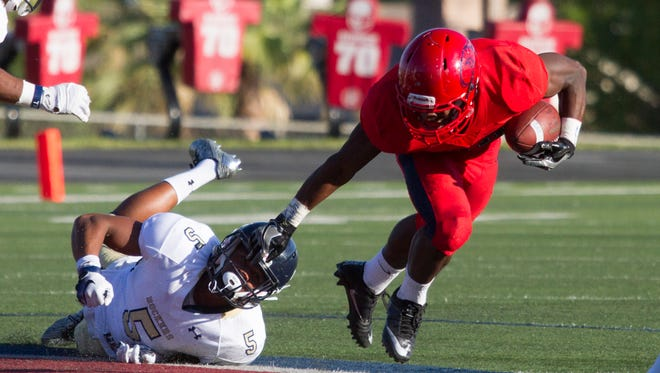 Dixie State running back Clifford Simms avoids a South Dakota School of Mines player during their game Saturday, Sept. 9, 2016.