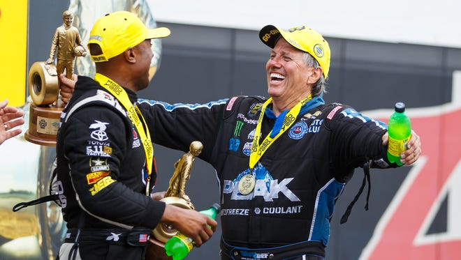 NHRA Funny Car driver John Force (right) celebrates with Top Fuel winner Antron Brown after winning the Carolina Nationals at zMax Dragway in Concord, N.C.