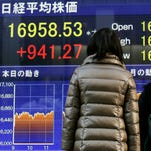 A mother and her daughter are watching closing information of Tokyo's Nikkei Stock Average in Tokyo.