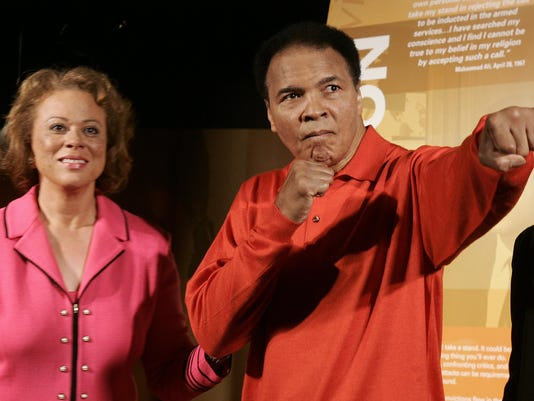 Muhammad Ali (R) strikes a boxing pose w