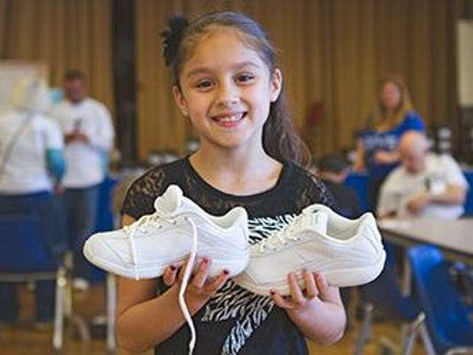 Girl holding shoes Soles4Souls