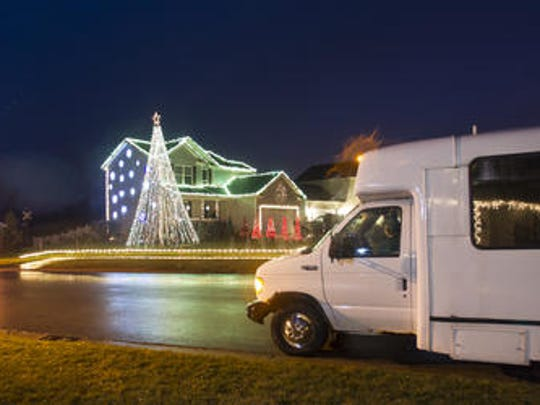 People in parked cars, including this bus from a local retirement home view the Brown family home on the corner of Fernwood and Cranbrook Lane in Delhi Township. It features 50,000 Christmas lights synced to a music track that viewers can tune into. This is the seventh and final year of the light show. The Browns are moving.