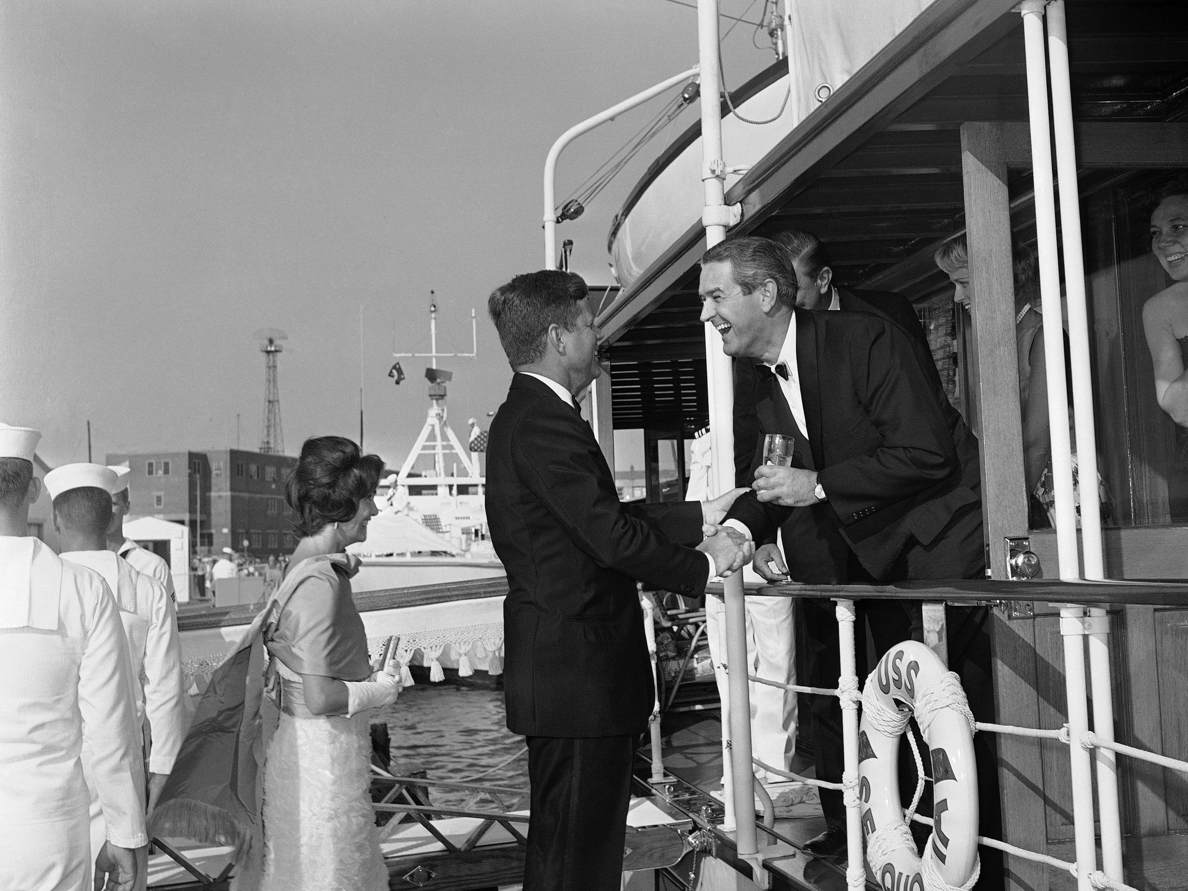 Secretary of the Navy John Connally Jr., leans over the rail of the yacht USS Sequoia to greet President John F. Kennedy at the Naval Weapons Plant dock in Washington on July 11, 1961. Mrs. Jacqueline Kennedy smiles as she speaks to Franklin D. Roosevelt Jr., hidden by Connally. Woman at right is unidentified. This preceded a cruise on the Potomac River to Mt. Vernon, Va., for a dinner given by the president and first lady for visiting President Ayub Khan of Pakistan. In background is the PT boat, Guardian, one of the vessels assembled to carry guests to the dinner site. (AP Photo/Byron Rollins)