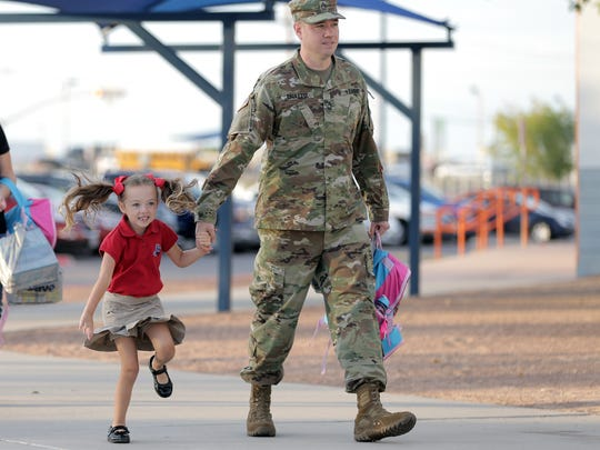 Maryanna Paulette, 5, bounces around out of excitement as she's escorted into John Drugan School for her first day of school by her father, Army Master Sgt. Josh Paulette. Socorro ISD and Gadsden ISD schools returned to returned to class on Monday.
