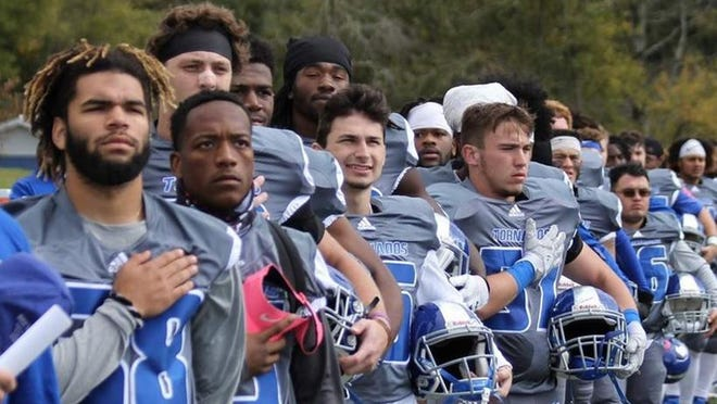Brevard College's football players salute the flag prior to a game last season.