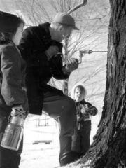 1956: Mason jars and a hand-drill are the tools of choice for this family-scale sugaring operation (subjects and location unknown).