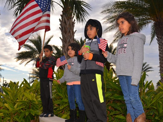 The children of Feras Alqawasmi,- Rashid,  Ayat, Mishary and Janat wave American flags while listening to speakers. Protesters gather Sunday evening at Exploration Tower in Port Canaveral to protest Donald Trump's immigration order.