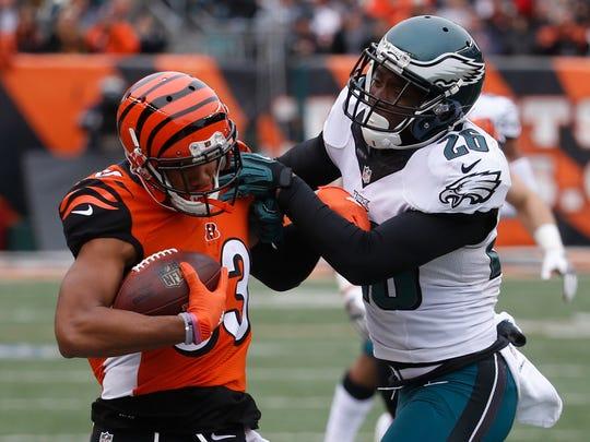 Cincinnati Bengals wide receiver Tyler Boyd (83) runs the ball against Philadelphia Eagles defensive back Jaylen Watkins, center left, in the first half of an NFL football game, Sunday, Dec. 4, 2016, in Cincinnati.