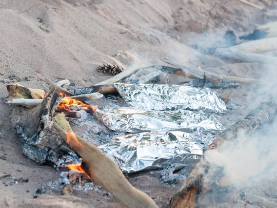 Campfire dinner on the beach consisting of whitefish in foil.